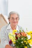 Femme aîné avec des fleurs Photographie stock libre de droits