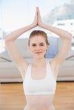 Femme avec des frais généraux jointifs de mains au studio de forme physique Photos stock