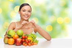 Femme avec des fruits et légumes montrant le coeur Photographie stock