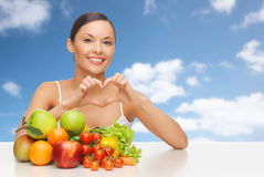 Femme avec des fruits et légumes montrant le coeur Image libre de droits