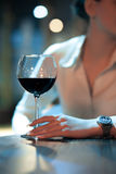 Femme avec des galss du vin rouge se reposant en café ; photographie stock libre de droits