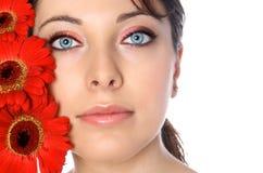 Femme avec des gerberas rouges Image stock