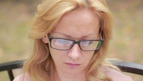 Femme avec des glaces affichant un livre Plan rapproché reflété dans les lentilles du livre banque de vidéos