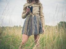 Femme avec des jumelles se tenant dans le pré image libre de droits