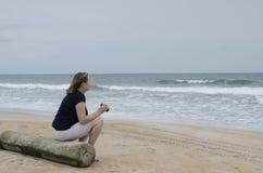Femme avec des jumelles sur la plage 2 Photographie stock libre de droits