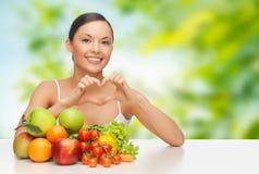 Femme avec des légumes montrant le coeur de main Images stock