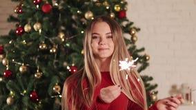 Femme avec des lumières de Bengale le réveillon de Noël Sur le fond de l'arbre de Noël banque de vidéos