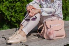 Femme avec des lunettes de soleil dans des mains se reposant sur un banc ? c?t? du sac rose en parc photos libres de droits