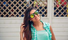 Femme avec des lunettes de soleil regardant l'appareil-photo au-dessus de la barrière de jardin Photos stock