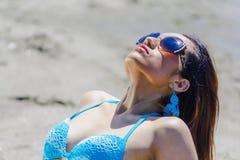 Femme avec des lunettes tout en prenant un bain de soleil Images stock