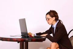 Femme avec des lunettes travaillant sur le premier ordinateur des genoux Image libre de droits