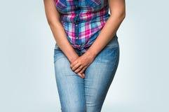 Femme avec des mains tenant sa fourche, elle veut faire pipi Image stock