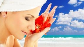 Femme avec des pétales de fleur au-dessus de fond de station de vacances Photos stock