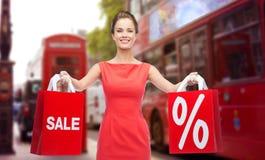 Femme avec des paniers au-dessus de rue de ville de Londres Photos stock