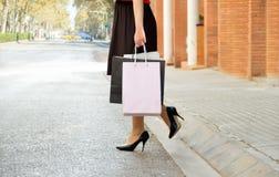 Femme avec des paniers dans la ville Images stock