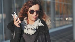 Femme avec des paniers marchant et parlant au téléphone portable banque de vidéos