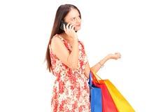 Femme avec des paniers parlant à un téléphone Photo stock