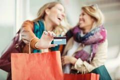 Femme avec des paniers tenant la carte de crédit Photographie stock