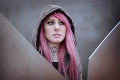 Femme avec des perforations et des tatouages roses de cheveux Image libre de droits