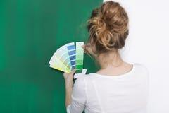 Femme avec des plats de couleur devant un mur vert Image libre de droits