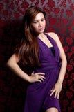 Femme avec des poses pourprées de robe Photographie stock libre de droits