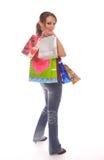 Femme avec des sacs à provisions regardant au-dessus de l'épaule Photos libres de droits