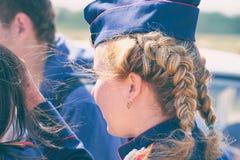 Femme avec des tresses dans l'uniforme dans un fourrage-chapeau photographie stock libre de droits