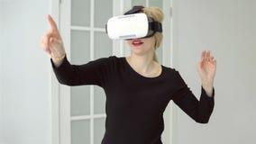 Femme avec des verres de réalité virtuelle ondulant ses mains photos stock