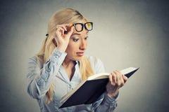 Femme avec des verres lisant regardant le livre choqué étonné Images stock