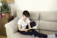 Femme avec des verres lisant un livre sur un sofa Image stock