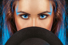 Femme avec des yeux bleus derrière le chapeau Photos libres de droits