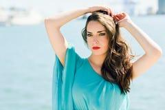Femme avec des yeux bleus portant la robe bleue dans la plage Images libres de droits