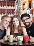 Femme avec deux amis mâles dans un café Images stock