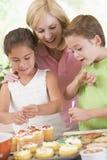Femme avec deux enfants décorant le cuisinier Image libre de droits