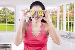 Femme avec deux tranches de kiwi frais Photographie stock
