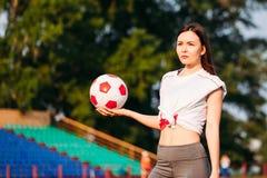 Femme avec du ballon de football dans des ses mains sur le terrain de football sur le fond des supports photos libres de droits