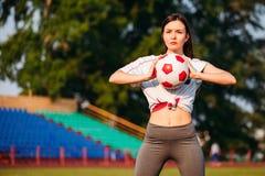 Femme avec du ballon de football dans des ses mains sur le terrain de football sur le fond des supports photo stock
