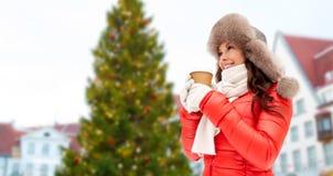 Femme avec du café au-dessus de l'arbre de Noël à Tallinn photographie stock libre de droits