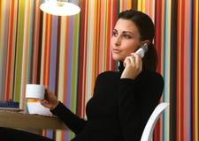 Femme avec du café et le téléphone portable Photographie stock libre de droits