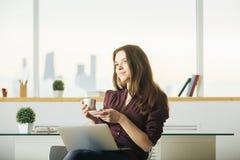 Femme avec du café potable d'ordinateur portatif images stock