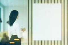 Femme avec du café regardant l'affiche modifiée la tonalité Images libres de droits