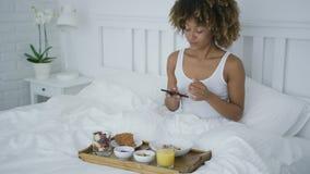 Femme avec du charme à l'aide du téléphone tout en prenant le petit déjeuner clips vidéos
