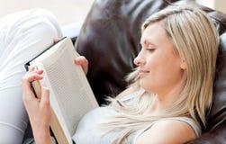 Femme avec du charme affichant un livre se reposant sur un sofa Photo libre de droits