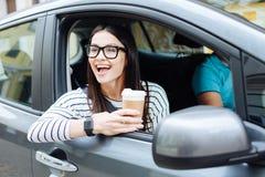 Femme avec du charme appréciant le café et la vue de la fenêtre de voiture Images stock