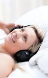 Femme avec du charme avec des écouteurs sur se trouver sur un bâti Images stock
