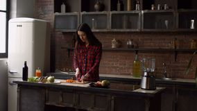Femme avec du charme coupant la carotte dans la cuisine banque de vidéos