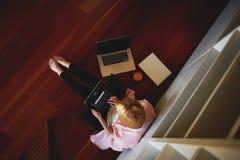 Femme avec du charme d'affaires travaillant de la maison tout en prenant le petit déjeuner Photo stock