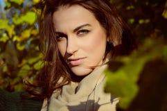 Femme avec du charme dans l'écharpe beige souriant sur ensoleillé Photo stock