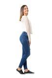 Femme avec du charme dans la chemise et des jeans tressés riant de l'appareil-photo Vue de côté Photos stock