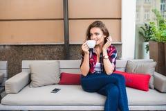 Femme avec du charme dans un café potable de café en café de rue Été photographie stock libre de droits